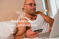 Picture of a man holding his credit card and shopping online while laying in his bed at home. The man has beard stubble, glasses, jewelry, and a tattoo.